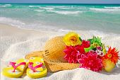 Pretty straw hat, flipflops, and flower bouquet on beach