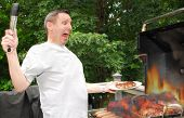Man grilling on barbeque when flames get out of control