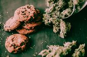 Chocolate Cookies With Cbd And Thc Are On A Black Table With Cannabis Buds. The Concept Of Marijuana poster