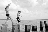 Young kids having fun on pilings at seashore