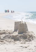 PERDIDO KEY, FL - JUNE 9: A sandcastle is shown as BP oil spill workers (background) clean the beaches on June 9, 2010 in Perdido Key, FL.