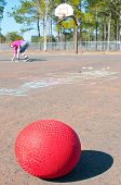 ball on playground with giirl writing chalk