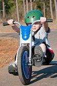 young boy riding trike with helmet