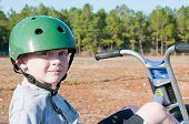 boy riding trike wearing helmet