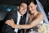 Portrait of newlywed couple smiling sitting in limousine