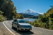Car Driving Near Mt Fuji In Japan With Motion Blur Showing Rapid Movement On A Highway Road At Lake  poster