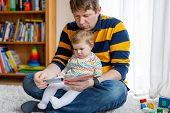 Young Father Reading Book With His Cute Adorable Baby Daughter Girl. Smiling Beautiful Child And Man poster