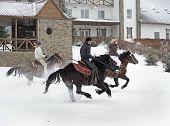 Three Cowgirls Go Horseback On Snow-Covered Village
