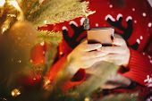Beautiful Girl Holding Smartphone And Browsing Internet Golden Christmas Tree With Lights And Presen poster