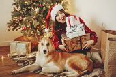Happy Girl In Santa Hat Holding Gift Boxes And Cute Dog Sitting At Golden Beautiful Christmas Tree W poster