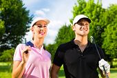 Young sportive couple playing golf on a golf course, they certainly do exercise or have training