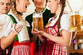 stock photo of stein  - Young people in traditional Bavarian Tracht in restaurant or pub with beer and steins - JPG