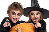 image of warlock  - Boy and girl wearing halloween costume with pumpkin on white background - JPG