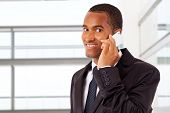 African American smiling businessman on the phone in his office