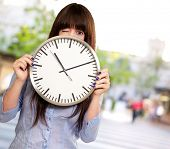 Woman Holding Clock Winking, Outdoor