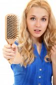 picture of pelade  - women with hair problem holding loss hair comb in hand - JPG