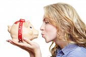 Attractive blonde woman kissing piggy bank on her hands