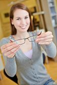 Happy female optician holding new glasses in retail store