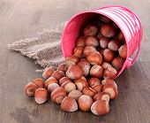 Overturned bucket with hazelnuts on wooden background