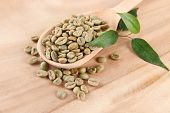 Green coffee beans in spoon and leaves on wooden background