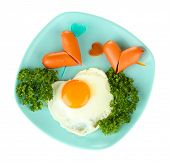 Sausages in form of hearts, scrambled eggs and parsley, on color plate, isolated on white
