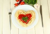 Cooked spaghetti carefully arranged in  heart shape and topped with tomato sauce, on  wooden backgro