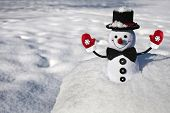 stock photo of ball cap  - Happy Christmas snowman  with black hat and  mittens in snowy ball - JPG