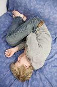 Young Blond Man Lying On The Bed