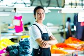 Worker or production manager standing proudly in a Chinese textile factory, it is his workplace