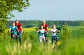 stock photo of bike path  - Family with three girls having a weekend excursion on their bikes on a summer day in beautiful landscape - JPG