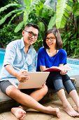 Indonesische paar in einer tropischen Umgebung, er arbeitet sie liest ein Buch