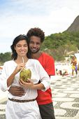 Multi ethnic couple of boyfriends friends tourists drinking coconut water on the edge of Rio de Jane
