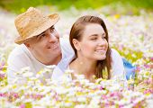 Closeup portrait of beautiful couple lying down on chamomile meadow and looking in one side, summer