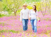 Two cheerful lovers walking in spring garden, having fun outdoors, relaxation on backyard, romance a