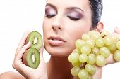 Artistic photo of beautiful young woman holding grapes and kiwifruit in hand, eyes closed.