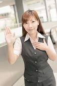 Asian business woman give you a gesture of swear, closeup portrait in outside of Taipei, Taiwan, Asia.
