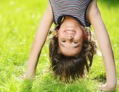stock photo of upside  - Portraits of happy kids playing upside down outdoors in summer park - JPG