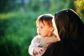 stock photo of muslim kids  - Middle Eastern Muslim mother playing with her little baby in green park and holding him in arms - JPG
