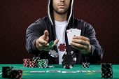 stock photo of poker hand  - Poker player on a red background throwing poker chips - JPG