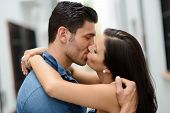 picture of heterosexual couple  - Attractive young couple kissing in the street - JPG