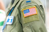 stock photo of camouflage  - Part of uniform of United States Air Force. Person wearing military clothes with pockets and national symbol. Focus on american flag in yellow frame attached to shoulder part of army clothing.