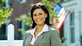 pic of real-estate agent  - A female real estate agents smiles at the camera outside - JPG