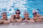 stock photo of swimming  - happy teen  group  at swimming pool class  learning to swim and have fun - JPG
