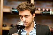 image of merlot  - Man tasting a glass of red wine - JPG