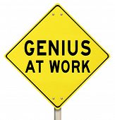 The words Genius at Work on a yellow road sign to give you warning that someone smart, brilliant, in