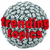 The words Trending Topics on a ball or sphere of hash tags to illustrate hot news, buzz or trends on