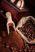 image of coffee grounds  - Coffee beans ground coffee vintage coffee mill and sack with coffee beans on brown wooden background - JPG