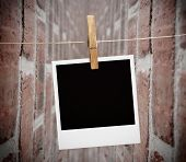 Instant print transfer hung with peg with bricks wall on the background