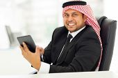 cheerful arabian businessman browsing internet on his tablet computer