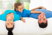 cute little girl tickling her father while family lying on bed at home